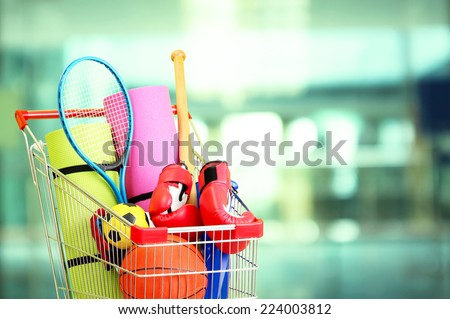 Shopping concept. Shopping cart with sport equipment on shop background