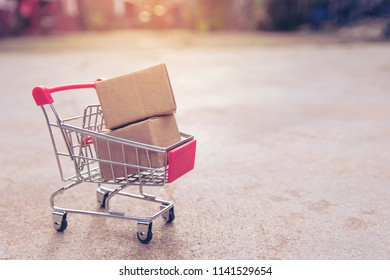 Shopping concept : Cartons or Paper boxes in shopping cart on concrete floor. online shopping consumers can shop from home and delivery service. with copy space