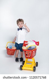 Shopping concept - child with shopping basket and shopping cart giving thumb up. Toddler boy with child supermarket cart. Shopping with little kids. Isolated. Copy space advertising store, supermarket