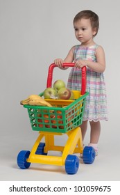 Shopping concept - child with shopping cart full with groceries