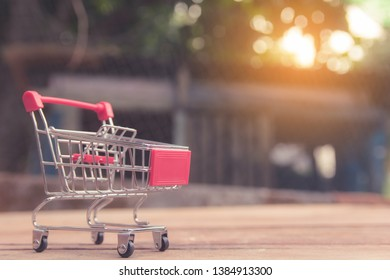 Shopping concept - Empty red shopping cart on brown wood table. online shopping consumers can shop from home and delivery service. with copy space
