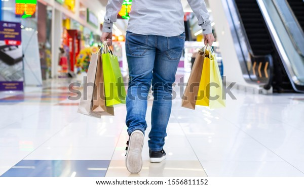 Shopping concept. Guy walking in shopping mall with paper bags, crop, back view