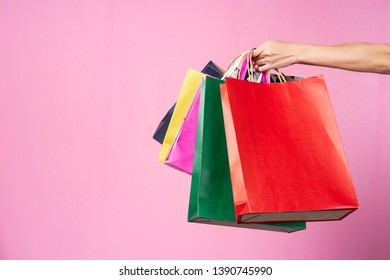 Shopping concept. Hand holding colorful shopping bags on pink background with free space.