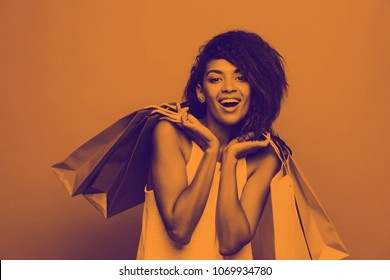 Shopping Concept - Headshot of Portrait young beautiful attractive African woman smiling and joyful with colorful shopping bag. Yellow Pastel wall Background. Copy Space and duotone
