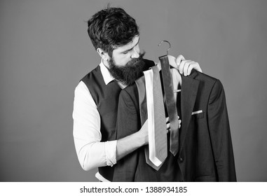 Shopping concept. Shop assistant or personal stylist service. Stylist advice. Matching necktie with outfit. Man bearded hipster hold neckties and formal suit. Guy choosing necktie. Perfect necktie.