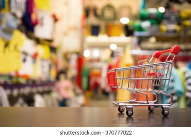 Shopping Concept : Small Red Shopping Cart In Clothing Store