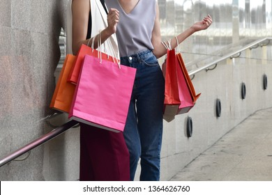 Shopping concept: Two women holding colorful shopping bag standing and talking together