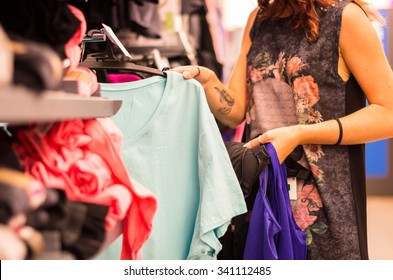 Shopping concept - woman choosing dress during shopping at garments apparel clothing shop