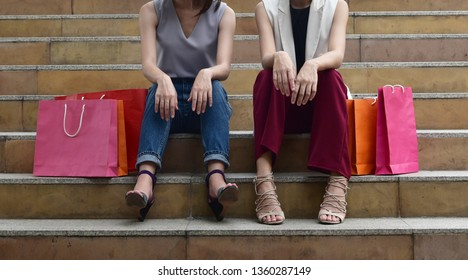 Shopping concept : Women sitting down on the stair together with  colorful shopping bags
