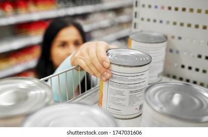 shopping, consumerism and people concept - woman taking tincan with food from shelf at grocery
