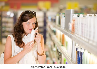 Shopping cosmetics - woman smelling bottle of shampoo in drug-store