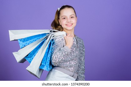 Shopping day. Child hold bunch packages. Kids fashion. Birthday girl. Favorite brands and hottest trends. Girl with shopping bags violet background. Shopping and purchase. Black friday. Sale discount.