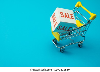 Shopping in department store, modern trade, hypermarket in lifestyle sale promotion season concept. Sale paper box in yellow supermarket trolley on blue background. Shopaholic love 50% off promotion