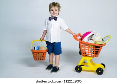 Shopping, discount, sale concept - cheerful little boy with shopping cart and basket. Kid plays in shop. Boy and shopping. Little kid in casual wear carrying child plastic shopping trolley. Copy space