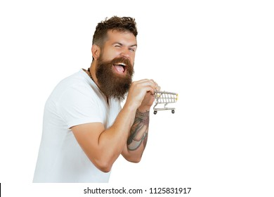 Shopping, discount, sale concept - cheerful bearded man with little shopping cart, basket. Smiling male with beard holding little market cart. Isolated white background. Sale consumerism in shopping