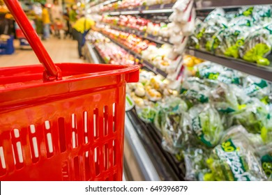 Shopping with empty red plastic basket in supermarket. Customer browses the goods in food and beverage department.
