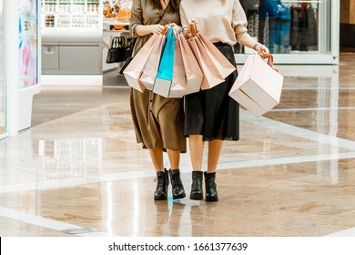 Shopping and entertainment, mall inside. Two beautiful girls with paper bags at the mall. The joy of consumption, Gift shopping, holiday