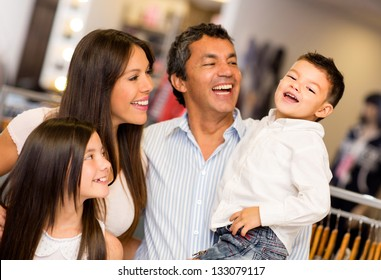 Shopping family looking very happy at a clothing store