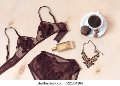 Shopping and fashion concept. Set of glamorous stylish sexy lace lingerie with chocolate sweets, morning coffee, woman accessories on wooden background