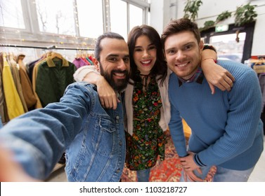 shopping, fashion and people concept - happy smiling friends taking selfie at vintage clothing store