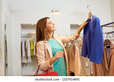shopping, fashion, sale and people concept - happy young woman choosing clothes in mall or clothing store