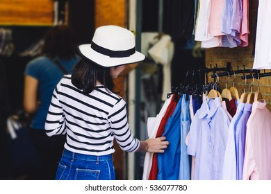 shopping, fashion, style and people concept - happy asian woman choosing clothes