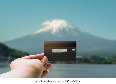 Shopping, finances, tourism, travel, concept. - Hands young man with show credit card over Mt.Fuji background in japan.