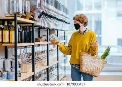 Einkaufen, Essen, Verkauf, Konsumentenkonzept. Blond kurze haarige Frau in Gesichtsschutzmaske hält Glas Glas mit Soja, Einkauf im Lebensmittelgeschäft Wiederverwendbare Korbweide Korb für den Einkauf. Konzept der Abfallvermeidung