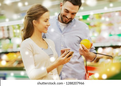 shopping, food, sale, consumerism and people concept - happy couple with smartphone buying oranges at grocery store or supermarket over snow