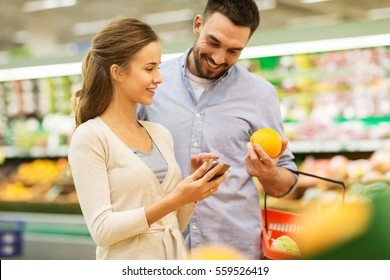 shopping, food, sale, consumerism and people concept - happy couple with smartphone buying oranges at grocery store or supermarket