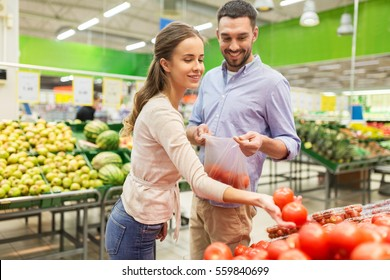 shopping, food, sale, consumerism and people concept - happy couple buying tomatoes at grocery store or supermarket