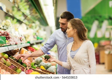 shopping, food, sale, consumerism and people concept - happy couple buying avocado at grocery store or supermarket