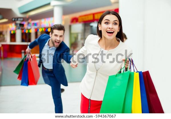 Es ist Einkaufs- und Vergnügungszeit. Porträt von fröhlichen glücklichen jungen, lieblichen Paar, das bunte Einkaufstaschen hält und in der Mall lacht. Konzept des Konsumerismus, Verkauf, reiches Leben.