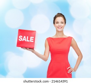 shopping, gifts, christmas and holiday concept - smiling young woman in dress with red sale sign