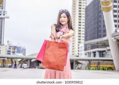 Shopping girl. Beautiful modern woman holding shopping bags. Background city