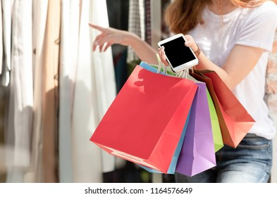 Shopping girl carrying  shopping bag with  smartphone in hand and other hand is choosing clothes.