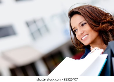 Shopping girl holding bags and smiling - outdoors