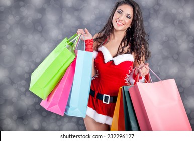 Shopping girl wearing santa claus clothes with color bag