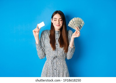 Shopping. Happy smiling woman looking satisfied with eyes closed, showing money dollar bills and plastic credit card, standing dreamy against blue background