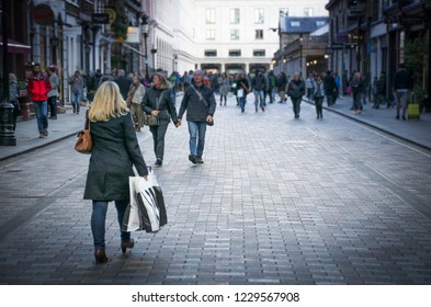 A shopping high street with anonymous people- blurred and vignetted