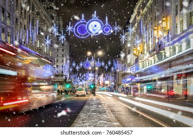 A shopping high street in London with christmas lights, blurred traffic and snowfall in winter