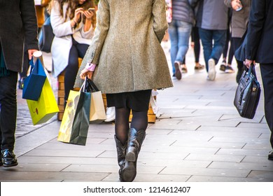 A shopping high street scene with woman carrying shopping bag