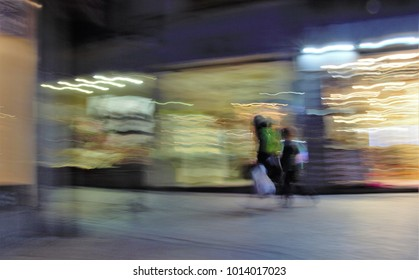 Shopping, Impressionist night photography of people taken at low speed, in a commercial street, with lights, ghostly shadows, panoramic, blurred background, motion sensation, semi-brutish people,