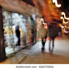 Shopping, Impressionist night photography of people taken at low speed, in a commercial street, with lights, ghostly shadows, panoramic, blurred background, motion sensation, semi-brutish person,