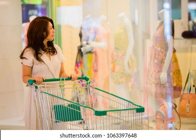 Shopping, Lifestyle Concept - Asian woman pushing shopping cart in shopping mall and Blurred image of clothes display in the fashion store. ( lens blur effect )