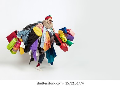 Shopping like an issue. Man addicted of sales. Overproduction and crazy demand. Female model wearing too much colorful clothes, need more. Fashion, style, black friday, sale, abusing purchases