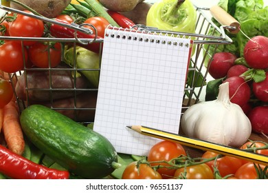 Shopping list with basket and fresh vegetables on a wooden background