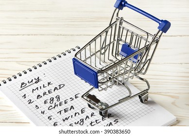 Shopping list and shopping cart on wooden background