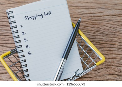 Shopping List, checklist to buy things from supermarket concept, pen with small note pad paper with handwriting headline as Shopping List and number listed in miniature basket on wooden table.
