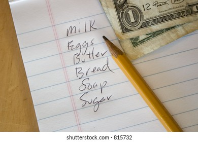 A shopping list on the table with a pencil and some dollars